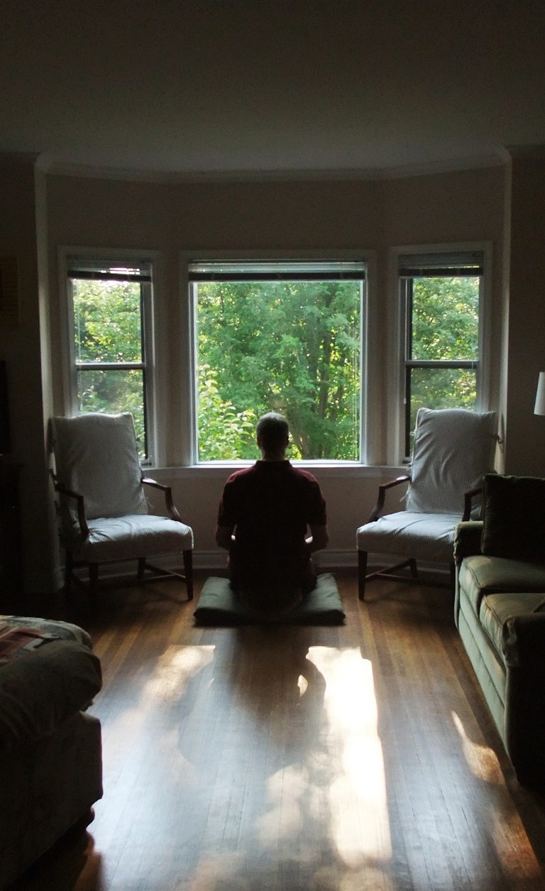 A photo of Karl sitting on a wood floor, meditating in front of a window that looks out over dense green trees.