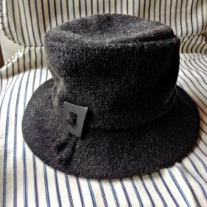 A photo of a dark grey structured 40's inspired wool hat.