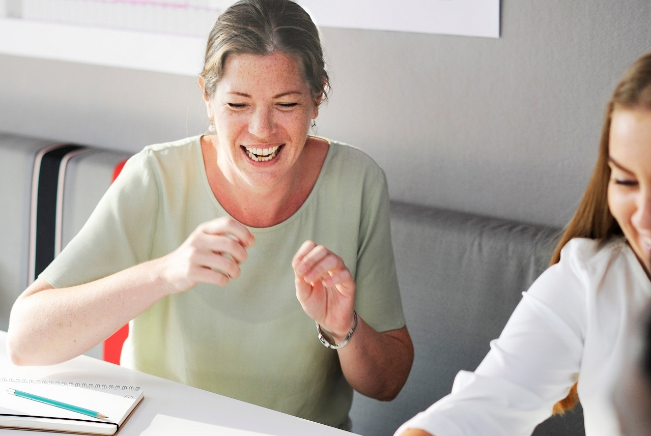 Older woman laughing engaged in discussion